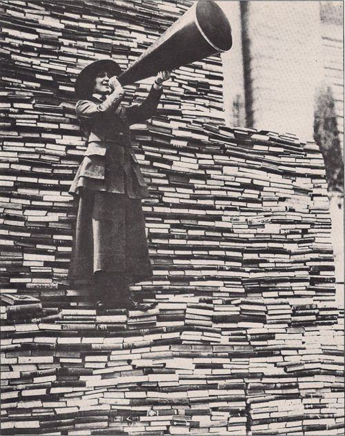 Standing on a mountain of already donated volumes, an amiable barker calls for still more books from passers-by outside the New York Public Library on Fifth Avenue.1910s