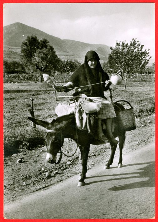 Greek woman riding a donkey and spinning.