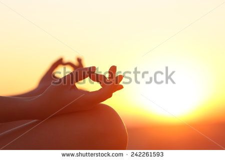 Back light of a woman hands exercising yoga at sunset with a warmth background - stock photo