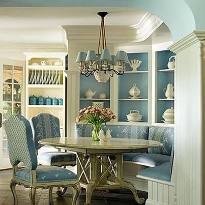 Pretty bright dining room with robins egg blue walls lots of crown molding cute little blue lampshades on the chandelier fabric chairs and a corner bench White cottage shabby