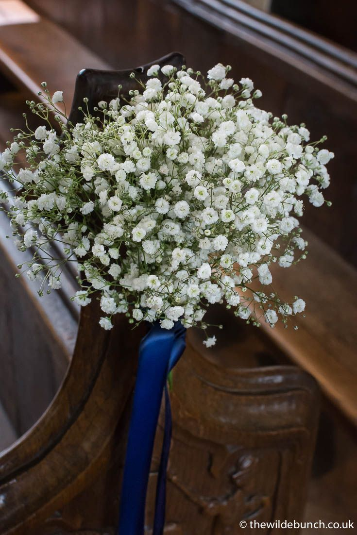 A classic Gypsophila pew end with deep blue ribbon to match the bridesmaid dresses. A Wilde Bunch wedding design at North Cadbury Court Church