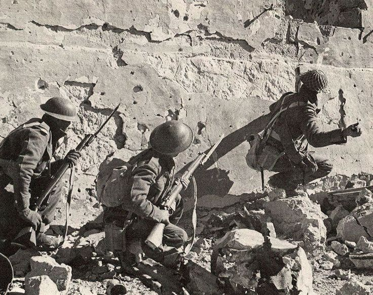South African soldiers at Sollum in January 1942 attacking a machine gun nest, equipped with grenades and Enfield rifles.