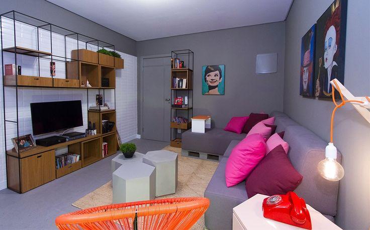 """""""Sala para 3"""": móveis e quadros de cores fortes quebram a sobriedade do cinza e dão um toque atual."""