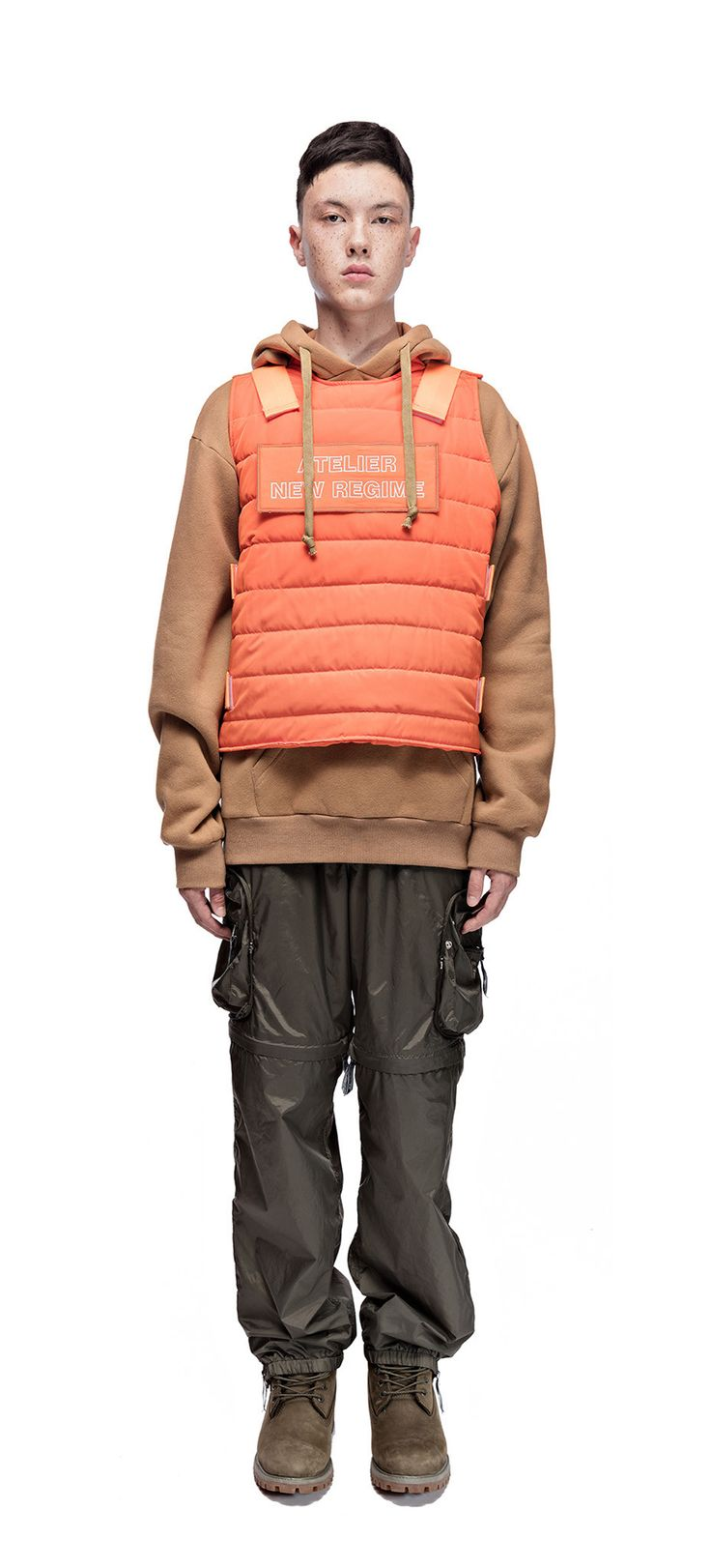 Atelier New Regime sleeveless quilted tactical style vest in orange. Features detachable velcro patch with white logo embroidery at front, and velcro straps at body. #ateliernewregime #newregime #FW16