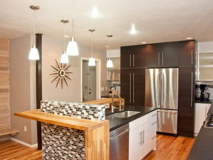 Appliances: Contemporary Kitchen With Hovering Wood Island. black kitchen appliances. black food processor. dark kitchen cabinet. white kitchen island. black countertop. wooden breakfast bar. gray wall. wood flooring. white pendant light. stainless steel refrigerator.