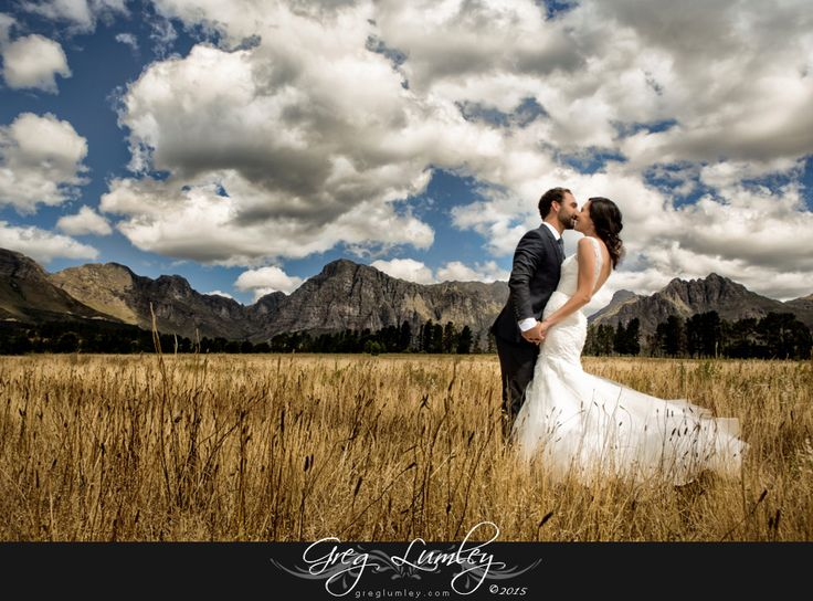 Wedding couples photo in field with stormy sky photographed in Ashanti