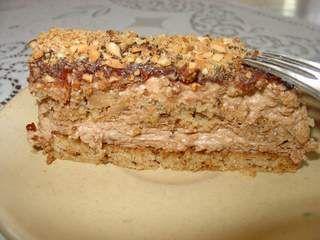 Recept za Posnu tortu sa čokoladom i kikirikijem. Za spremanje torte neophodno je pripremiti brašno, griz, šećer, prašak za pecivo, ulje, kiselu vodu, rum, sok od pomorandže, puding, čokoladu, margarin i kikiriki.