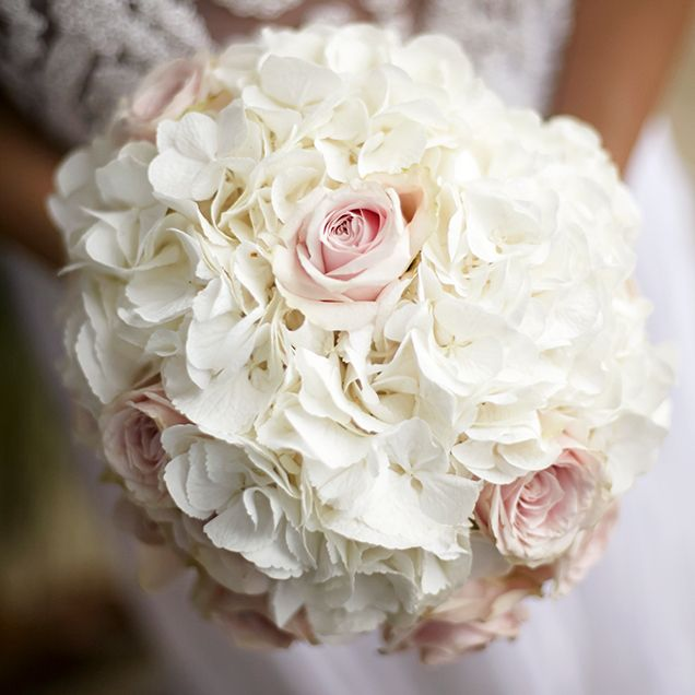 Monique carries a breathtaking wedding bouquet of white hydrangeas and pale pink roses.