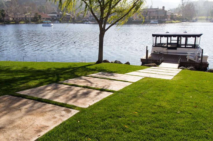 Concrete paver slabs make a pathway to the home's dock. What's your favorite lake memories? #backyardideas #backyarddesign #backyarddecor #backyardlandscaping
