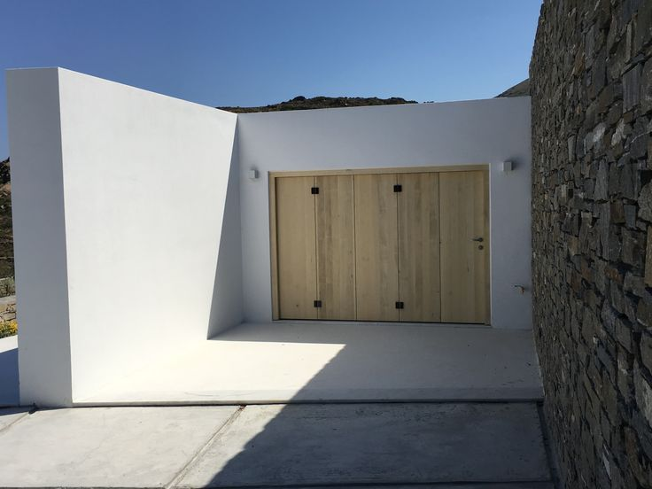 "Accoya Alder wood for garage door. No treatment intervention in the wood in order to ""age"" normally by the climatic conditions. Summer residence in Paros island Greece"