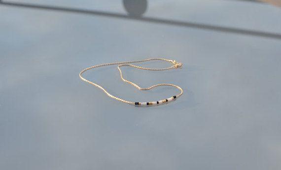 Collier chaîne minimaliste serpentine en gold filled 14k, fait en France Perles Miyuki Delicas 11/0, perles en verres très fines et régulières du Japon. 38 cm en tout, couleurs noir, blanc mat, et doré Personnalisable en longueur ou couleur de perles, nhésitez pas à me contacter. Envoi soigné sous enveloppe bulle et prêt à offrir. La finition gold-filled en Or 14 carats est appliquée sur une base en laiton, avec un poids d'or de 50 à 100 fois supèrieur à un produit plaqué or. Les b...
