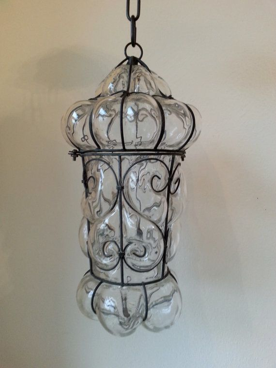 This is a stunning, Vintage Seguso Murano bubble wire wrapped clear glass cage pendant light. It has a puffy look to it with a fancy black steel metal cage. It has a removable top section, in order to replace the bulb.  This one was wired into a ceiling fixture box, but I have removed the wiring, as it didn't fair as well over time as the actual lamp.  It measures 17 long by 9 in diameter at the widest point. There is a 6 original chain attached. It is not wired - original wiring was…