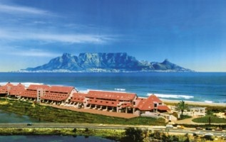 View of the Dolphin Beach Hotel with Table Mountain in the background. http://www.south-african-hotels.com/hotels/dolphin-beach-hotel/