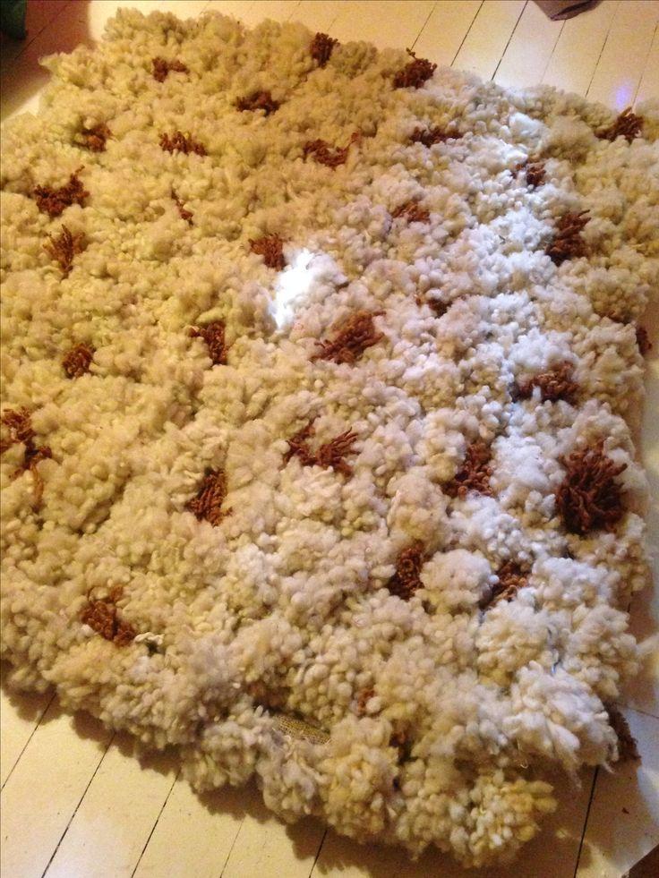 alfombra hecha con pompones de lana natural y rústica de oveja