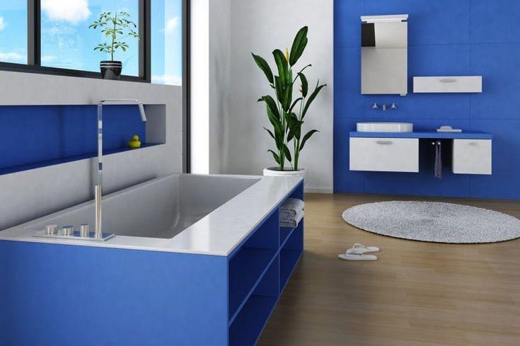 Aménagement d'une salle de bain aux allures bleu indigo avec sa baignoire et ses rangements à serviette, son plancher en bois et son tapis gris au sol