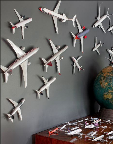 Planes on the wall! This would be cool with that magnetic paint - attach a small magnet on the back of each one and voila! Draw or paint a runway or some clouds or something...