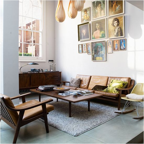 late 60's inspired room - love the paintings and the buffet under the large window. gorgeous furniture (eames chair?)