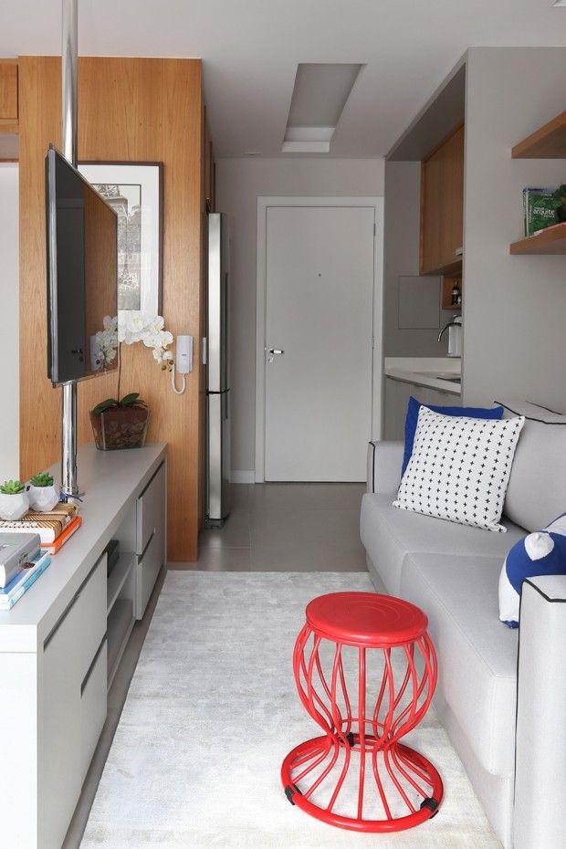 Cozinha integrada com a sala. Móvel baixo dividindo espaços. Prateleiras sobre o sofá. Mesa de apoio que é um banco. Projeto: Marcio Campos