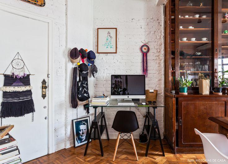 home office na sala de estar, com parede de tijolinho branco e mesa de cavaletes