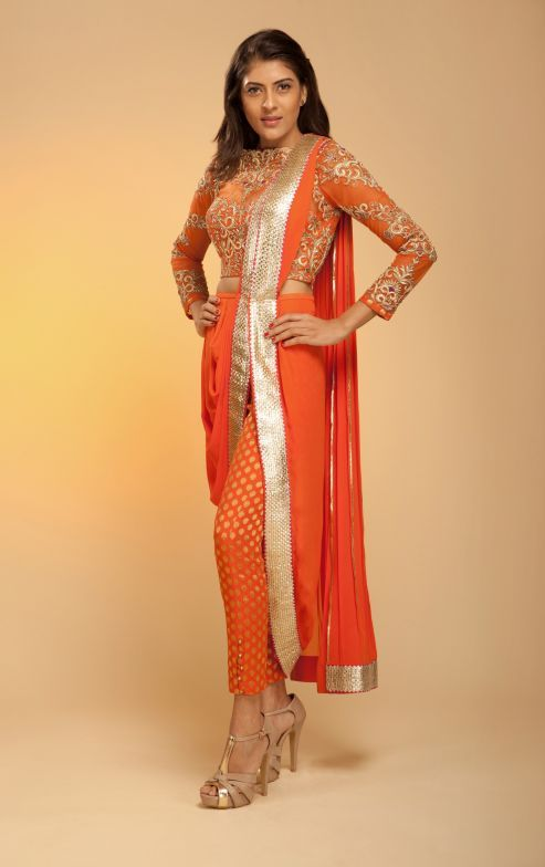 Twirl around on your sangeet and cocktail function in this racing orange khada dupatta concept saree. The saree comprises khada dupatta in georgette racing orange with gold gota border. A racing orange colour high neck full sleeves fitted bodice in tulle with gota, resham, dabka and zari is hand embroidered. The inner lining of the tulle choli is gold and racing orange self woven Banarasi silk fabric and creates magic with georgette buti cigarette pants in flaming orange colour.