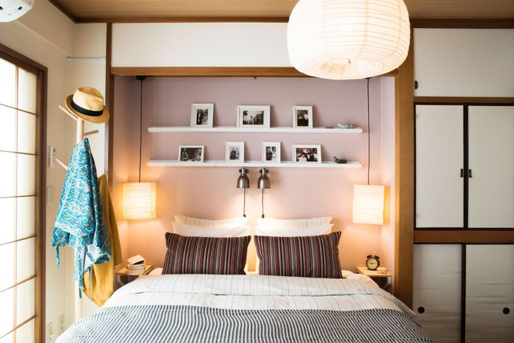 Blick auf ein Doppelbett, Leuchten, Bettwäsche, darüber RIBBA Bilderleisten in Weiß. Darauf sind Familienfotos zu sehen.