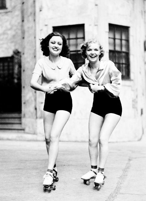 Dos bellas y jóvenes patinadoras de finales de la década de los 30, luciendo su lindura y su alegría de vivir, mientras una enseña a la otra a deslizarse sobre ruedas.