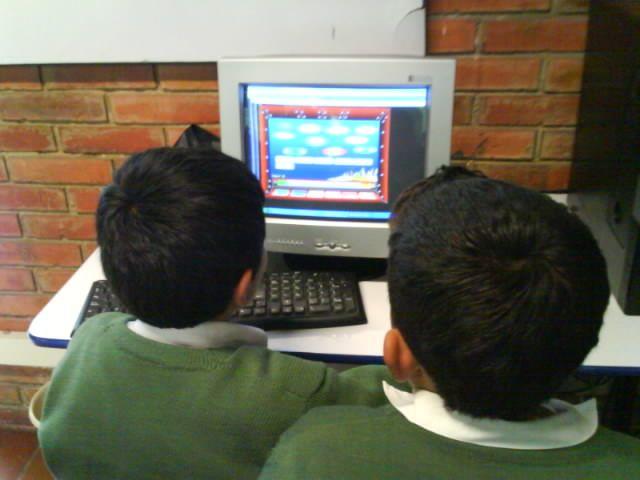 Fotografía sin rostro. Niños aprendiendo a través recursos multimedia.