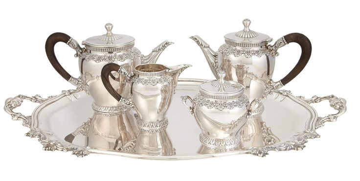 Italian Silver Coffee and Tea Service Peruzzi In the transitional Rococo/Neoclassical style, comprising a coffee pot with an ebony handle, teapot with an ebony handle, two-handled covered sugar bowl, creamer with an ebony handle and an oval two-handled tray, each decorated with bands of chased and repoussé acanthus leaves.