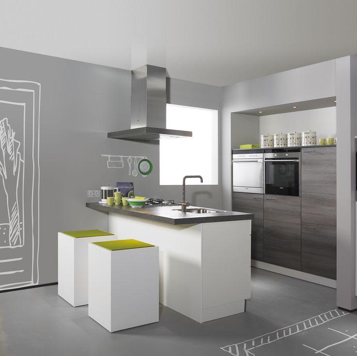 Keuken Natalia/Amica. Een speelse combinatie van stijlen. Zelfs is een compacte woonruimte past een eiland keuken! De lage vrijstaande kasten in hoogglans wit zijn afgewerkt met een stoer dik werkblad. Net zoals het werkblad zijn de halfhoge inbouwkasten uitgevoerd in modieuze grijze eiken-look.
