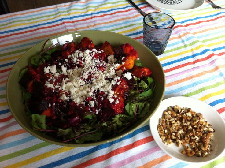 Gemengde salade met rode biet, rode ui en zoete aardappel uit de oven met een blauwe bessen dressing en fetakaas en walnoten