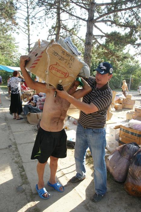 Челябинец Михаил Щапов помогает местному жителю донести гуманитарную помощь до дома