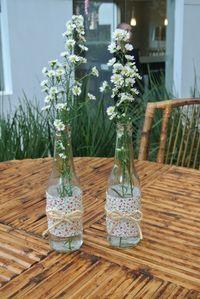 A empresa Mog & Mug (www.mogemug.com.br) utilizou garrafas vazias de vidro, decoradas com tecido floral, para acomodar minimargaridas, que foram dispostas no centro das mesas dos convidados desse aniversário