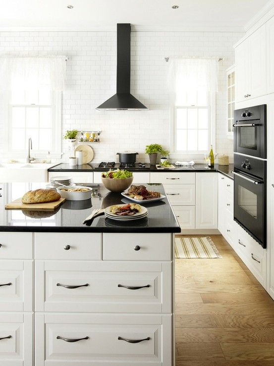 Beautiful Black and white Ikea kitchen design featuring Ikea Lidingo cabinets paired with black countertops as well as white subway tile backsplash