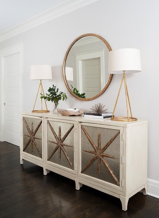 Beautifully appointed bedroom features a Melange Star Power Console topped with 2 Nina Tapered 1 Light Table Lamps in Gilded Iron with Natural Paper Shades positioned on either side of a round gold mirror mounted to a light gray wall lined with white crown molding.