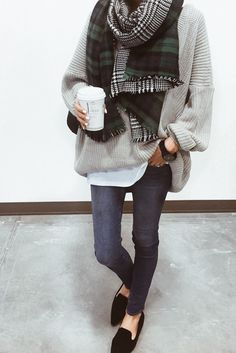 So comfortable and stylish. Get the look with an oversized plaid scarf, gray sweater, jeans, and loafers.