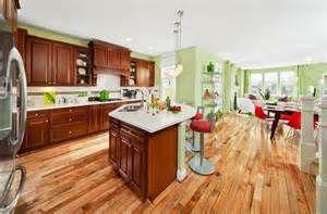green walls, wood cabinets, light wood floor