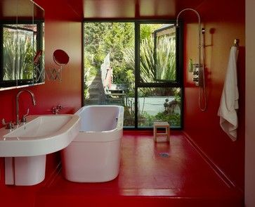 This bold red bathroom is clad in a commercial-grade epoxy paint, for waterproof surfaces that are easy to clean.