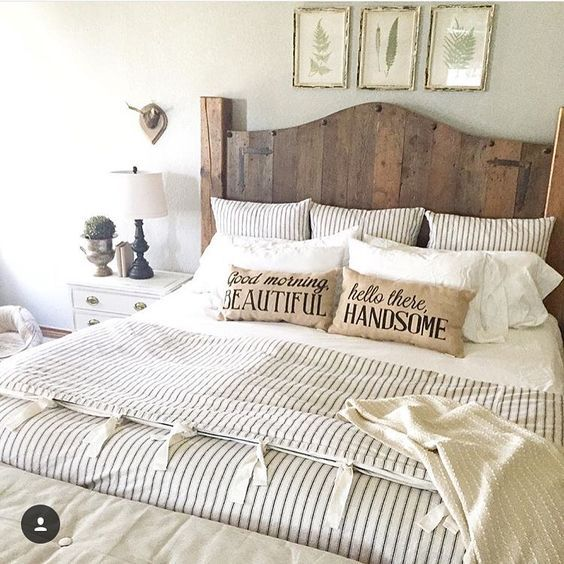 Farmhouse bedroom with striped duvet, burlap pillows and wood headboard.