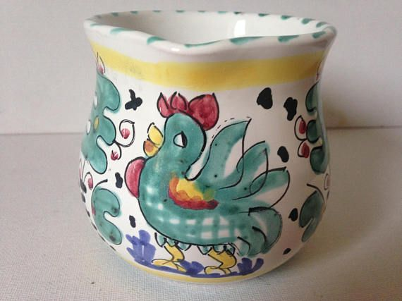 Sweet little Italian deruta milk jug/creamer.  This charming Italian Deruta jug is decorated with a gloriously handsome teal coloured rooster to the front of the jug surrounded by a matching floral design teal pattern on both sides.  Beautiful bright, sunny yellow trim, with matching teal stripes to the rim and stripes of vibrant red to the handle.  A gorgeous little jug, perfect for a serving milk on your breakfast cereal and just the thing to cheer up the breakfast table, even on a dul...