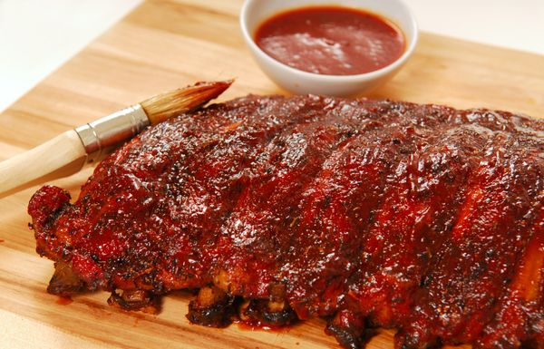 Oven-Baked BBQ Ribs (Serves 6-8)...   1/2 c. Brown Sugar,  2 T. Paprika,  2 T. Fajita Seasoning,  2 tsp Garlic Salt,  1 tsp Chili Powder,  Salt and Pepper to taste,  2 racks Pork Spare Ribs,  favorite BBQ Sauce,  1 c. Beer...