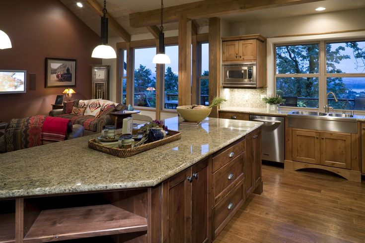 Rustic kitchen as part of a lodge home with dark hardwood, a large living room window, stainless steel appliances and pendant lights over the new kitchen island. Click on the image to see the hottest kitchen colors. #dreamkitchen #iwant #homeremodeling