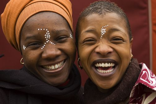 Africa |  Smiling South African women with body paint adornment on their faces.  Photo taken in Cape Town by Annie Griffiths Belt for the National Geographic.