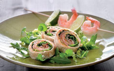 Lakseruller med flødeost og spyd med rejer og lime på en bund af salat