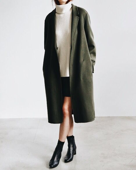 White sweater, leather black skirt, ankle leather black boots with long dark-green coat in winter outfit