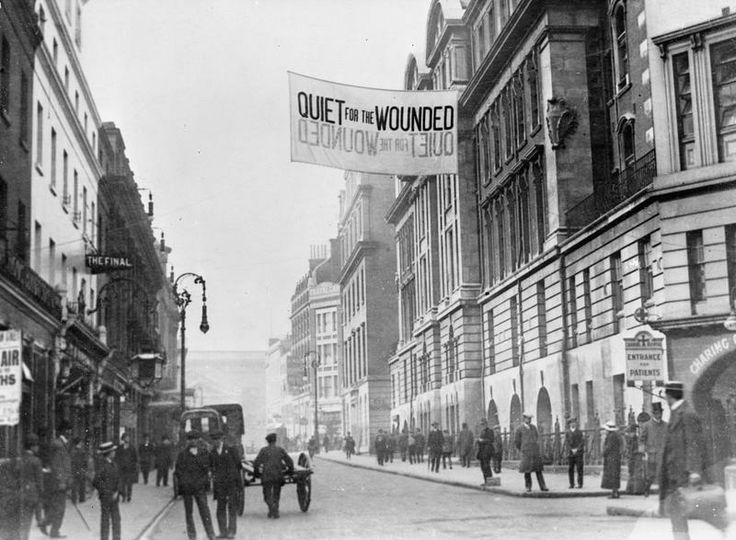 A large sign requesting 'Quiet for the Wounded' hangs outside Charing Cross Hospital at Agar Street, London, in September 1914. Heavy traffic has been diverted to minimise noise in the street.