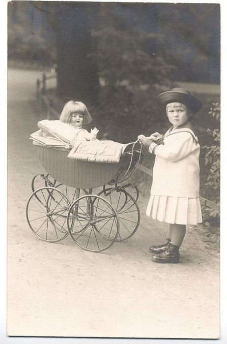 Vintage photo of little girl with her doll in baby buggy / pram.