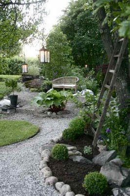 Gravel path & boxwood balls, love the ladder and the lanterns hanging from the trees!