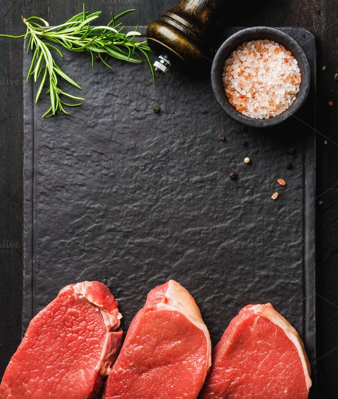 #Raw beef Eye Round steaks  Raw beef Eye Round steaks with spices and rosemary on black slate stone board over dark wooden background top view copy space