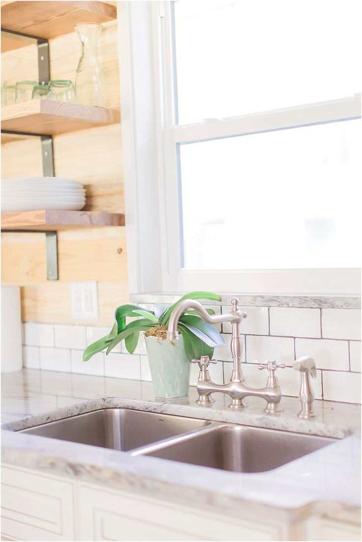 Jack and Jill bridge faucet over stainless steel sink and grey granite.  Open shelves and natural wood shiplap boards.  White subway with charcoal grout.