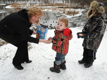 Feeding feathered friends in Barrie - Connie Campbell brought her grandchildren Blake, centre, and Keith Pleli to share some Rice Krispies with the ducks who make the pond their winter home, but weren't swarmed by the ducks the way they usually are.